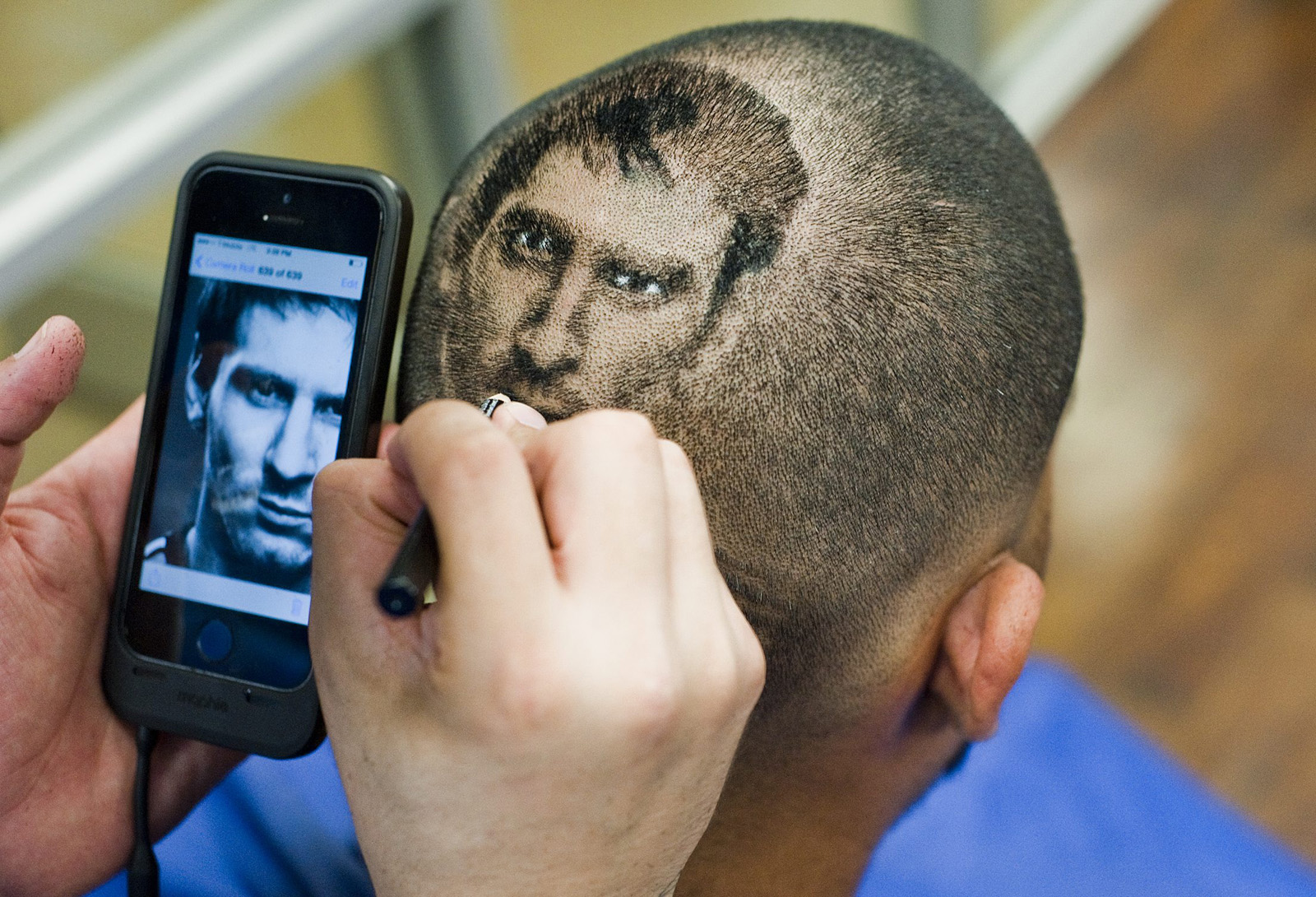 "Hair Artist and Master Barber Rob Ferrel, known as ""Rob the Original"" cuts the likeness of Argentine soccer player Lionel Messi on the head of customer Vincent Hernandez, ahead of tomorrow's World Cup match between Argentina and Switzerland at his barbershop in San Antonio, Texas June 30, 2014. REUTERS/Ashley Landis (UNITED STATES - Tags: SOCIETY SPORT SOCCER)"